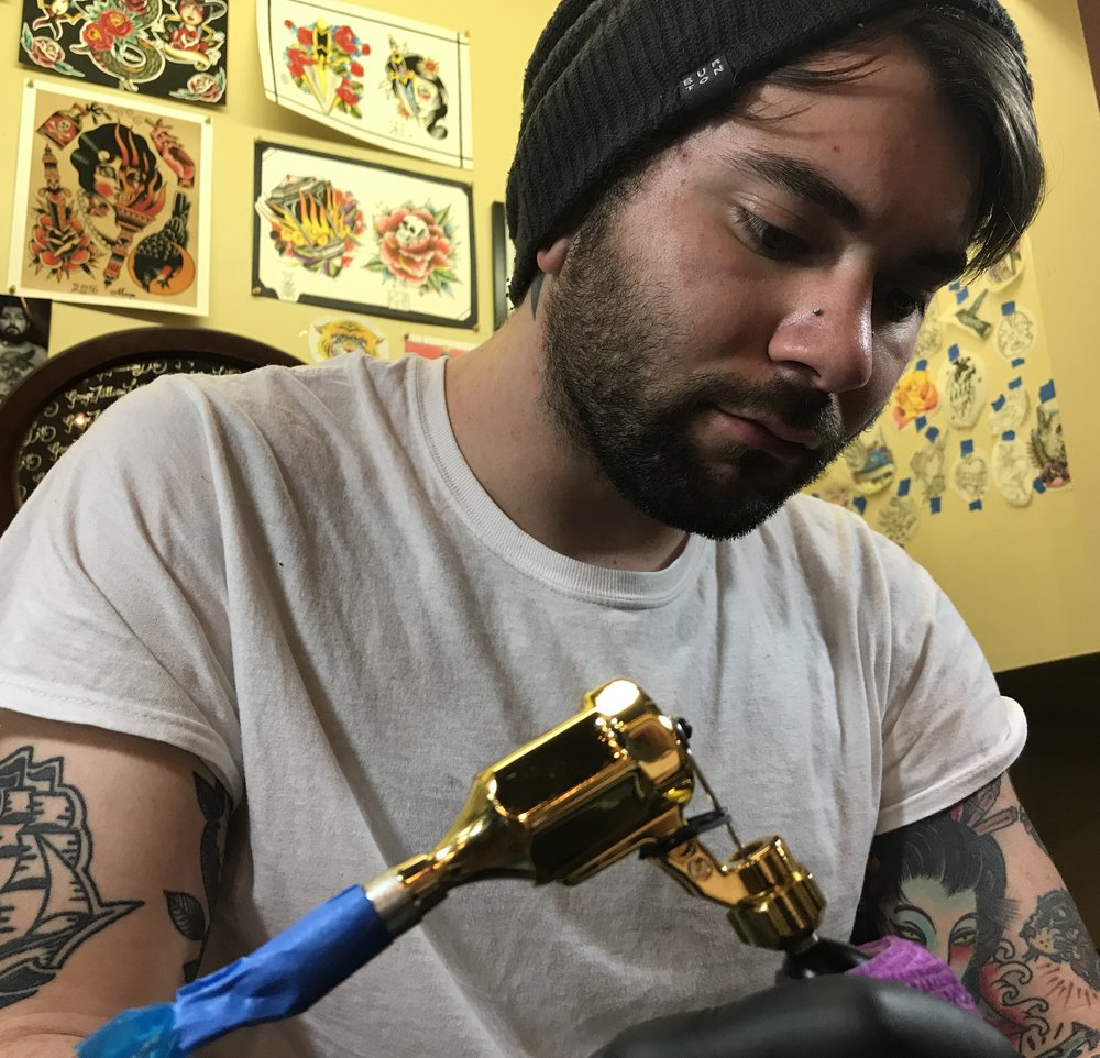 Killian Huckstead - Killian has been tattooing for 3 years. He enjoys doing bold traditional pieces with intriguing color palettes. Killian also enjoys doing dotwork and pepper shading techniques for more of a blackwork style. Click his photo to check out his work!