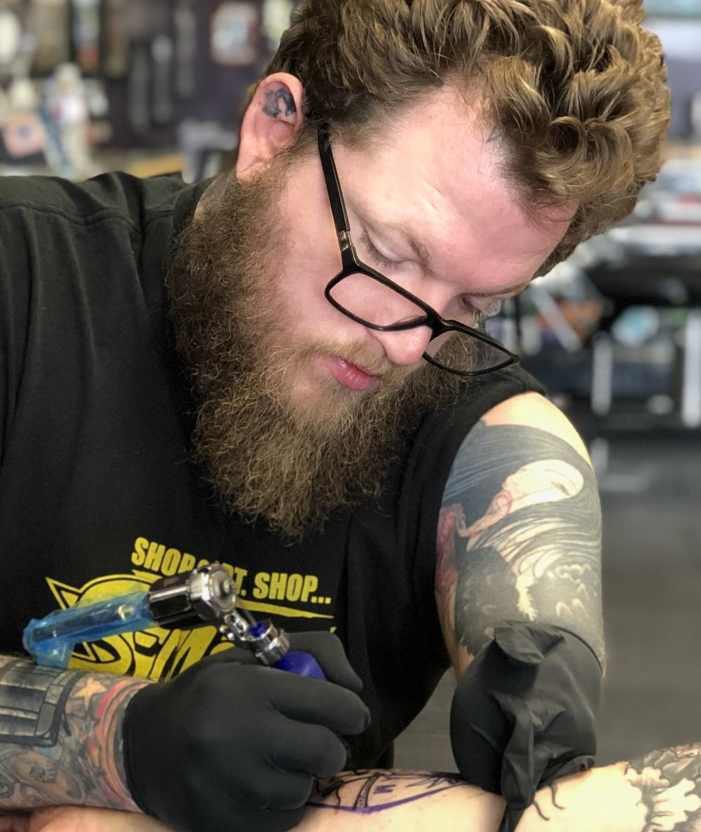 Bubba Carnline - Bubba is a Houston based artist with ten years under his belt and no left hand. He enjoys traditional, neo traditional, realism, and animation styles of tattooing. Click his photo to check out his work!