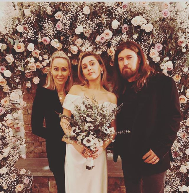 IN LOVE with Miley's floral archway n bouquet! 🌱 The bridal flowers contain spiral gum, anemones, sea holly, paper daisies & native wild flowers 💐 A simple archway of roses and baby's breath framed the fireplace. 💐 📸 via @tishcyrus ~ ~ ~ #miley #billyraycyrus #weddingday #bridalbouquet #flowerstagram #weddingdress #viviennewestwood #weddingday #tennessee