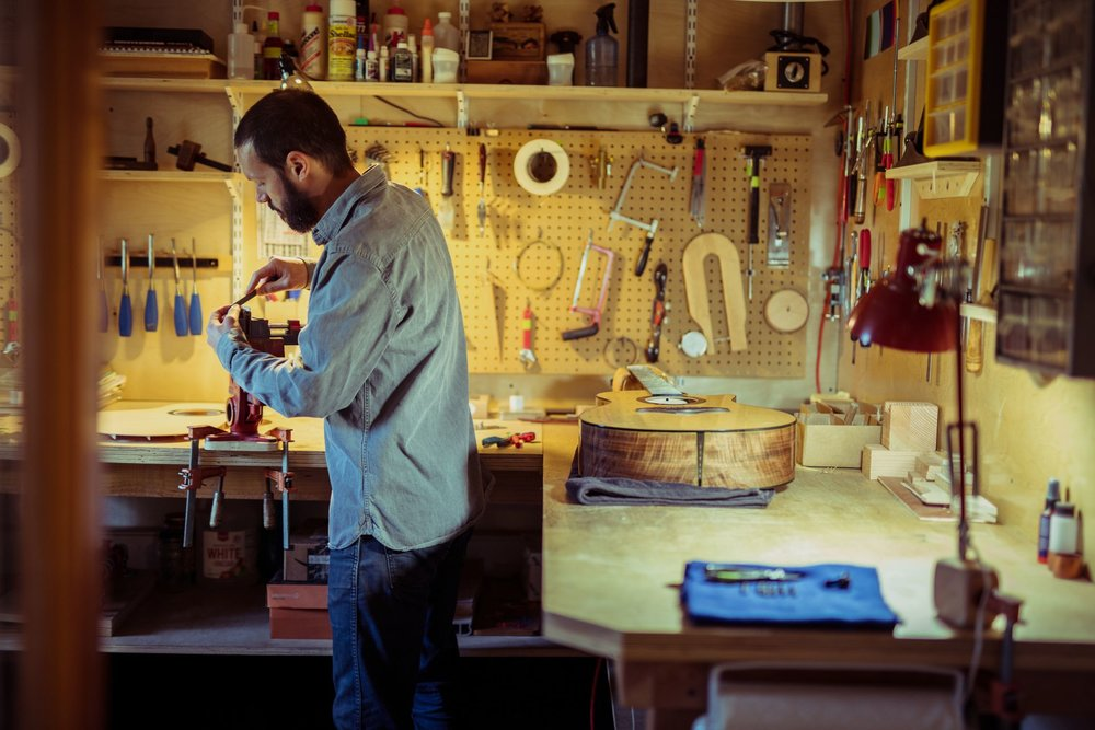 Luthier Mark Gaiero working on a custom acoustic guitar saddle at his workbench.