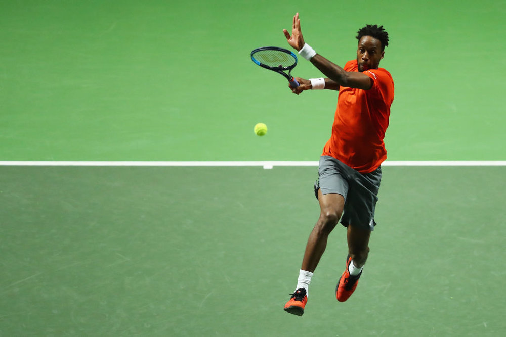 Gael Monfils smashes a forehand return as he jumps in the air.