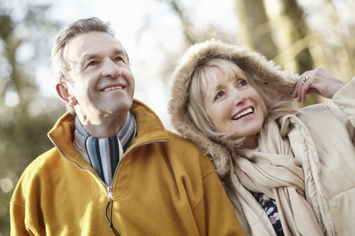 Older couple smiling outdoors following dental implant treatment for missing teeth