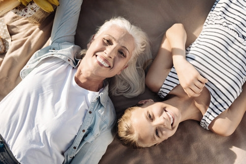 Grandmother lying in the sun with granddaughter following dental implant treatment at Redcliffe Dental Practice in Wirral