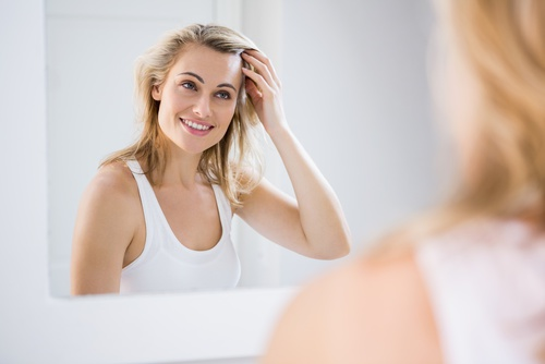 Blonde lady smiling in the mirror following home teeth whitening