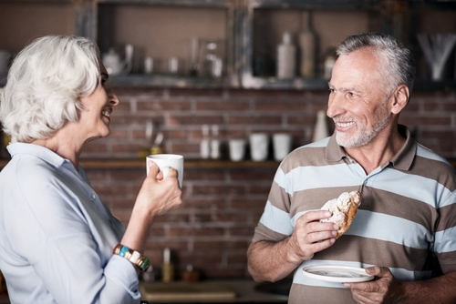Older couple in kitchen after restorative prosthodontic dental treatment