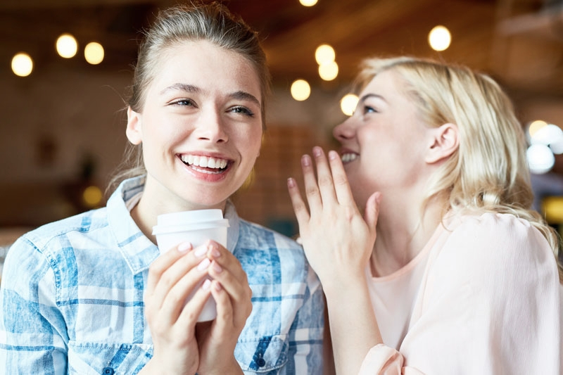 Copy of Young female friends smiling and drinking coffee following teeth whitening dental treatment
