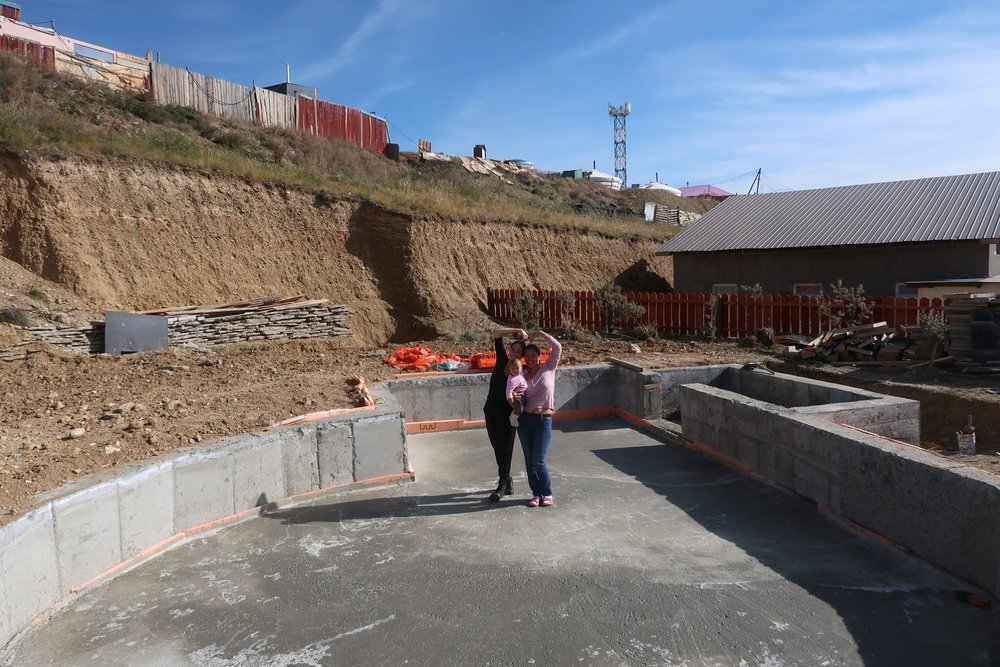 Tuya, her daughter, and I standing in the poured foundation of their future home in September 2018.