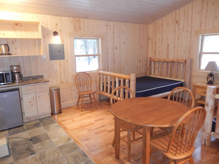 """Inside the cabins at Arrowhead provincial park. One bunk bed and one double bed, mini-fridge, kitchen table and microwave makes for extremely comfortable """"Glamping""""."""