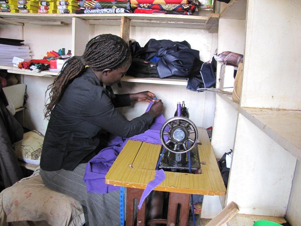 """Weduwe Florence kan nu voor haar gezin zorgen - """"Ik woon in het dorp Kamuma, vlakbij de stad Oyugis. Mijn man overleed in 2015 aan de gevolgen van aids. Hij liet mij achter met een dochter en twee zoons. Mijn kinderen hebben een tijd gebrek gehad aan eten en medische zorg. Omdat we de vereiste schoolspullen niet konden betalen, konden ze ook niet naar school. Ik had geen werk en kon geen baan vinden omdat ik de vaardigheden daarvoor miste. Ik besloot mee te doen aan een vakopleiding bij OIDO in Oyugis. Ik volgde trainingen in het maken van kleding en kleinschalig ondernemerschap. Daarna besloot ik om de twee naaimachines te gebruiken die ik van mijn man had geërfd (hij was kleermaker). Ook kon ik geld gebruiken van een groeps-spaarpot. Ik startte een kleine kleermakerswinkel in Oyugis. Ik verdien nu voldoende geld met het maken van schooluniformen en kleding en met kledingreparatie. Ik ben nu vrij van de zorgen die ik eerst had: ik kan eten voor mijn kinderen kopen, medische kosten betalen en schoolmaterialen voor mijn kinderen kopen. Ik weet nu hoe ik de prijs van mijn producten moet bepalen zodat ik, zonder echtgenoot, voor mijn gezin kan zorgen. Dit dankzij de training, de initiatiefnemers en ondersteuners van dit grootse project. Ik ben niet langer bang voor het leven maar ik sta nu voldoende in mijn kracht om uitdagingen in het leven aan te gaan."""""""