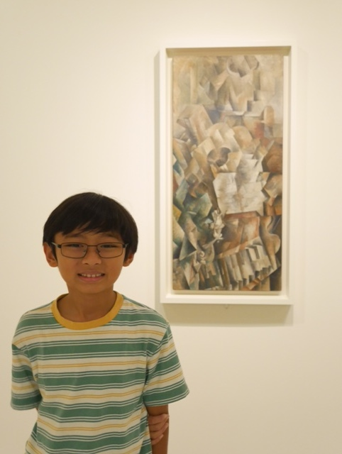 "Nathan standing next to Georges Braque's painting titled ""Piano and Mandola"""