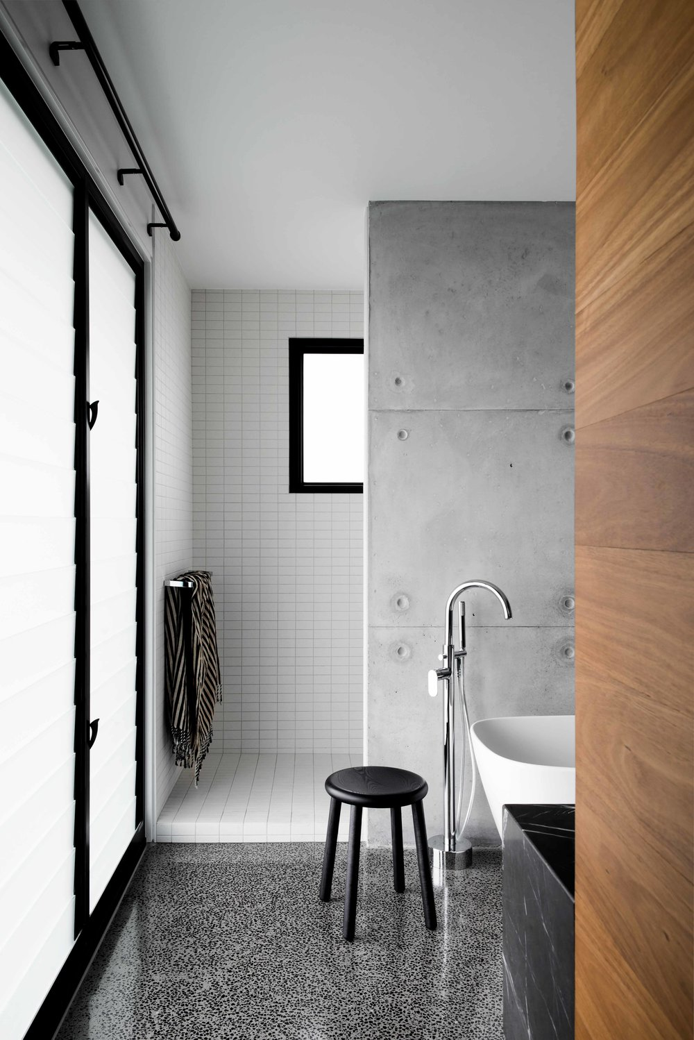 The bathroom continues in black and white tones of modern industrial style‭.‬