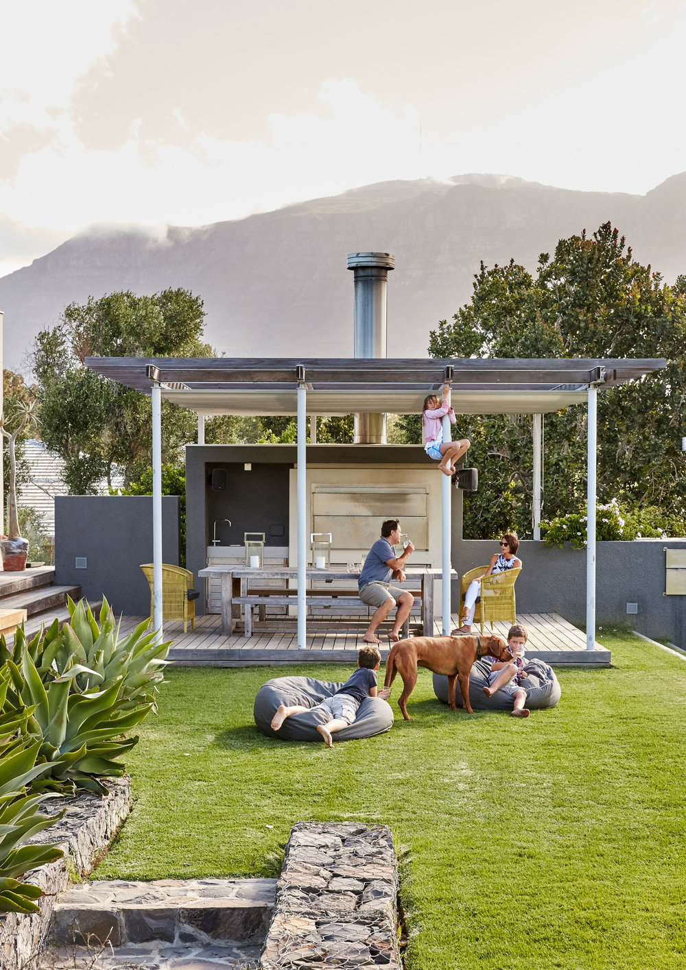 THIS LOW-SLUNG FAMILY HOME BORDERING CAPE TOWN'S GROOT CONSTANTIA WINE ESTATE WAS RAISED ON TONS OF SOIL SO THAT IT COULD TAKE ADVANTAGE OF ITS SPECTACULAR SETTING, THE VIEWS OF THE VINEYARDS AND THE MOUNTAINS BEYOND.