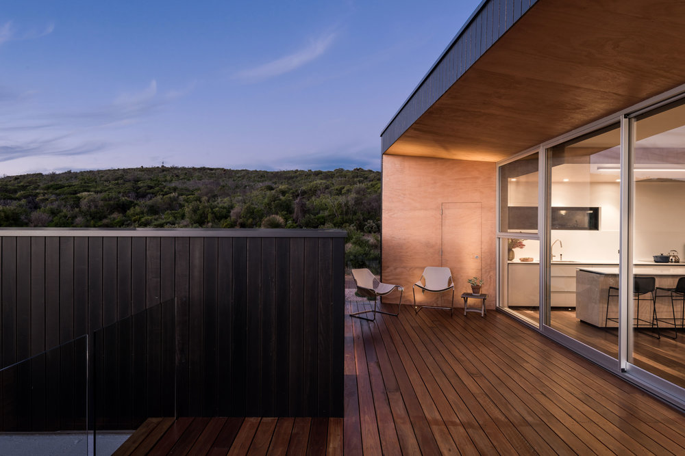 The upper level spotted gum deck is concealed between two pods‭. ‬Pacific teak clads the exterior‭, ‬while a rough sawn plywood lines the raked reveals to the main glazed doors‭. ‬The view to the east looks toward national parkland‭. ‬