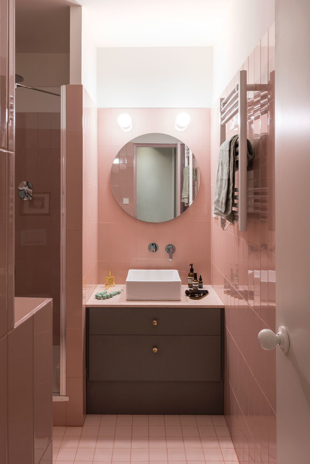 The master bathroom follows the subtle pink palette‭ , ‬clad with vertical 10x30cm ceramics by Ribesalbes and 10x10‭ ‬floor tiles by  Vogue‭. ‬All the counters are made with a pink terrazzo-like quartz finish‭.‬