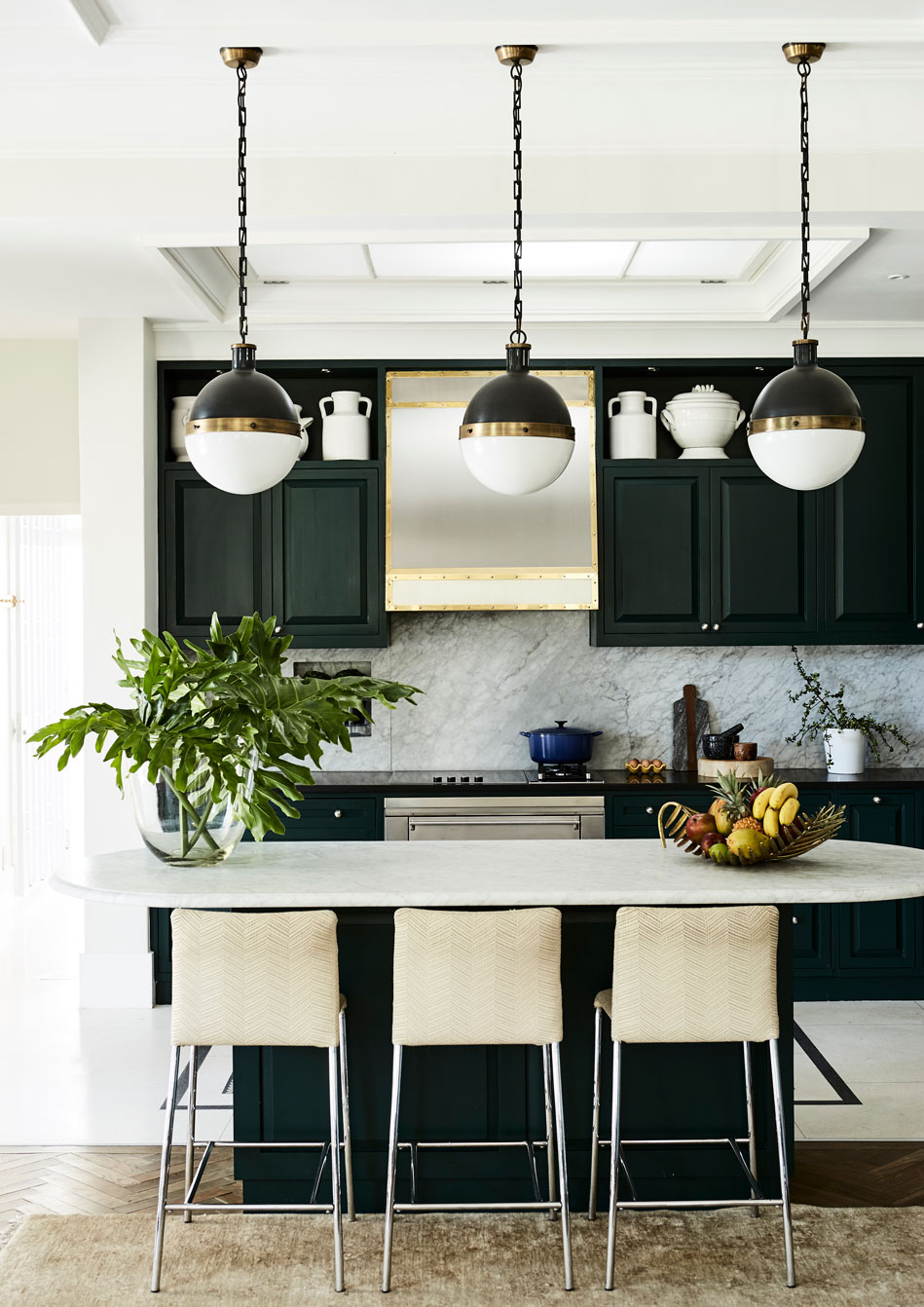 The built-in kitchen cabinetry is painted a dark shade of green‭ ‬‮$‬ع‭ ‬an unusual choice that forms a lovely counterpoint to the charcoal-grey mantelpiece and fireplace on the other side of this large‭, ‬open-plan room‭. ‬The joinery is by Nicolwood Custom Made Furniture‭ & ‬Kitchens in Wynberg‭, ‬Cape Town‭ (‬021-761-8735‭), ‬and the Hicks pendant hanging lights were sourced in the USA‭ ‬‮$‬ع‭ ‬designed by Thomas O'Brien of Aero Studios‭ (‬aerostudios.com‭), ‬they are fast becoming classics‭. ‬At the marble-topped kitchen island are‭ ‬three custom-made counter stools covered in durable woven raffia‭.‬