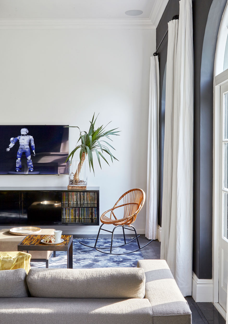 A black lacquered unit, vintage bamboo rocking chair and Italian Minotti corner sofa in the TV room that steps down from the kitchen. The tiger!&s eye and metal side table is by South African sculptor James B Hannah. 