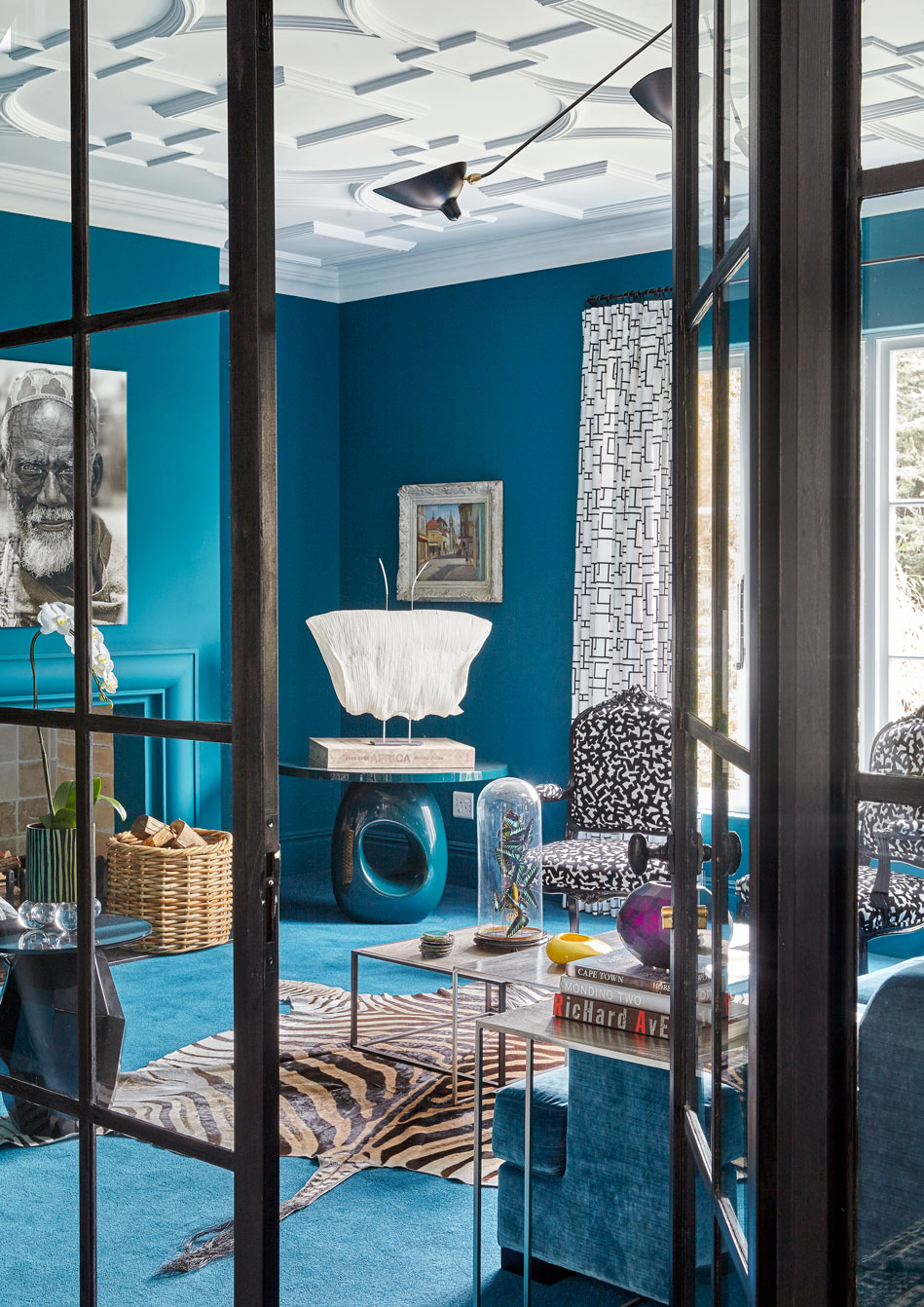 The teal blue wall hue was matched to the custom coloured Rowley & Hughes carpet in the living room. The family's sofa from Brussels was reupholstered in Mark Alexander empire fabric – also matched to the carpets. The metal French doors were installed. The ceiling lights are original Serge Mouille.  The black and white Fauteuil style chairs in the living room were lacquered and reupholstered in a Diane von Furstenberg-type dress print.  Plaster Art did the ceiling mouldings. The owner cut out a magazine clipping of an example of the moulding she had in mind.  The faceted table is the 'joker' and the hollow base table the 'vera cruz', both by India Mahdavi.