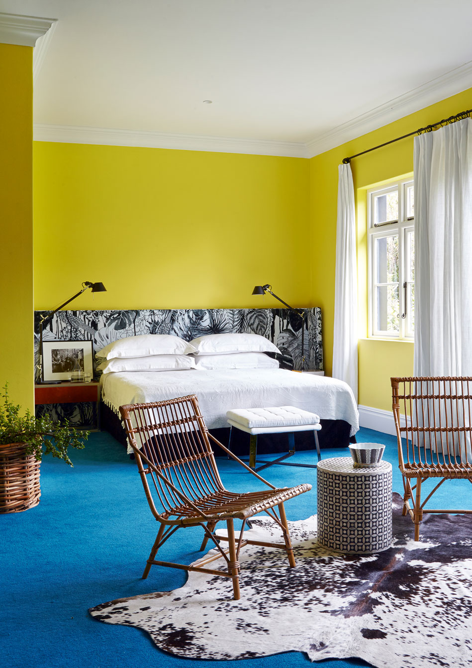 The guest suite features a custom made headboard upholstered in Christian Lacroix fabric, vintage bamboo chairs and a Nguni skin on the floor. 