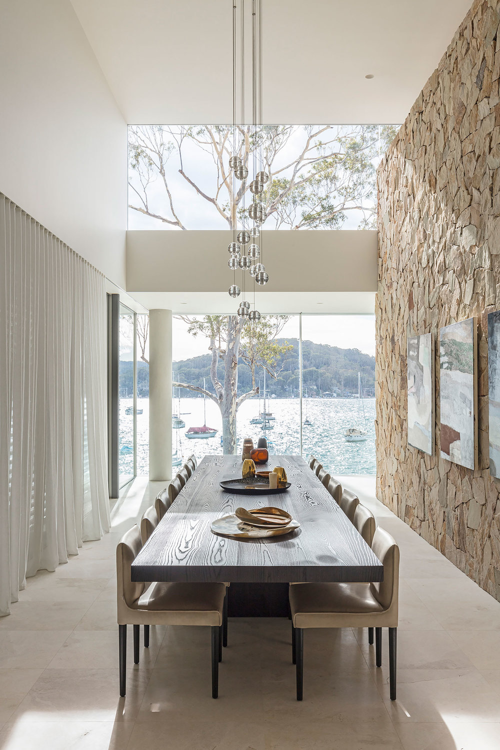 Particularly inspired by the 'hues and textures of the area's 'sand, bush and water', the home features creamy, whitish-grey in-situ concrete walls, bleached European Oak and limestone flooring, soft sandstone-coloured stack stone feature walls, and 'invisible' floor to ceiling Vitrocsa glass.