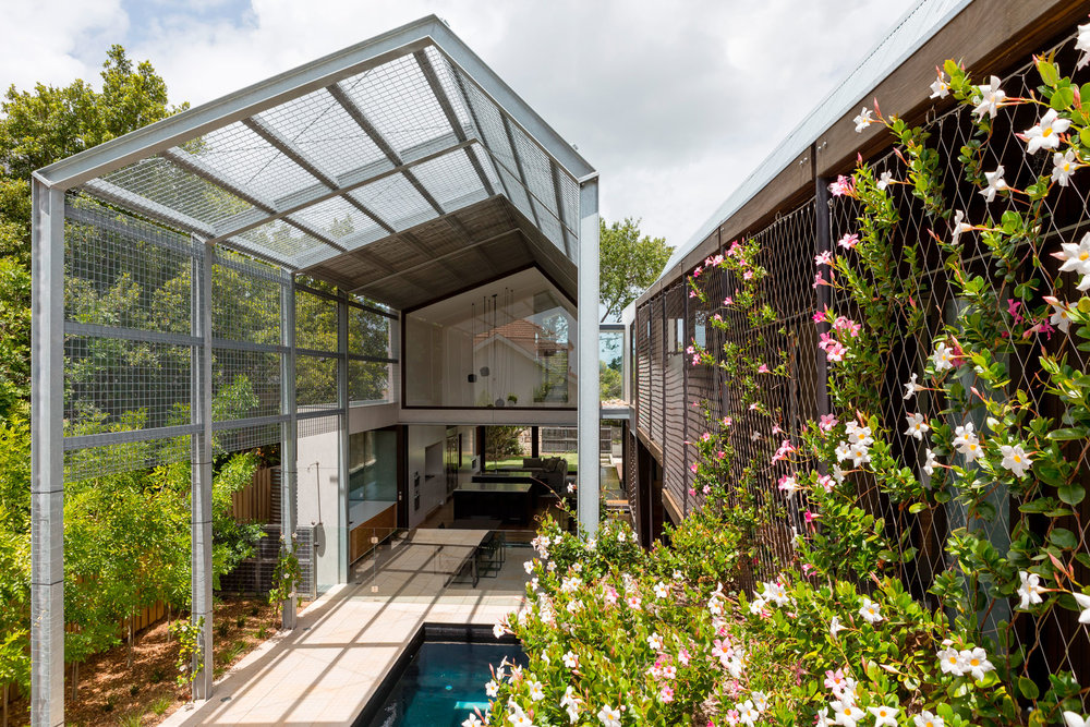 Climbing vines soften the building when viewed from the pool area while pink flowers highlight the structural western red cedar.