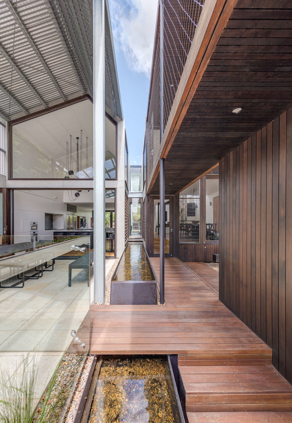 The house is divided into two pavilions by the water feature which provides a focal point, provides ambience and moderates seasonal temperature variations.