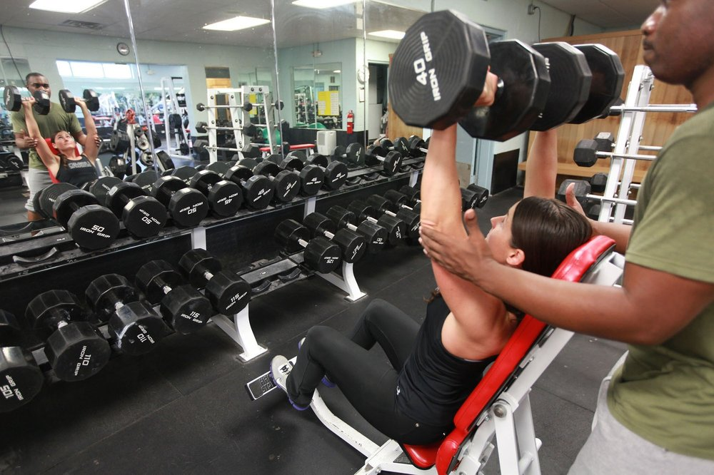 """Contrary to popular belief , a larger, stronger muscle is a more toned muscle. Working up to a 40lb overhead db press like this woman will increase """"tone"""", whatever that is."""