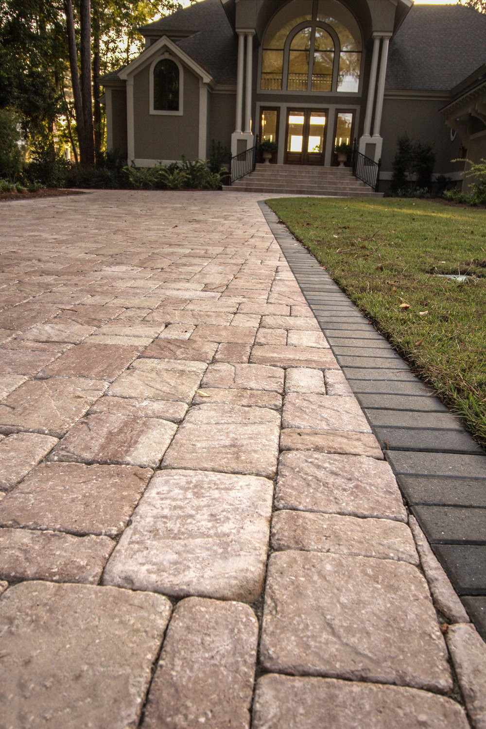 Many of our clients enjoy the Old World look and feel of tumbled brick pavers.  This paver driveway on Hilton Head Island, SC  used a Tremron 3pc Roma tumbled paver, in Sand Dune. Classically paired with a standard 4x8 non tumbled border. Beautiful!