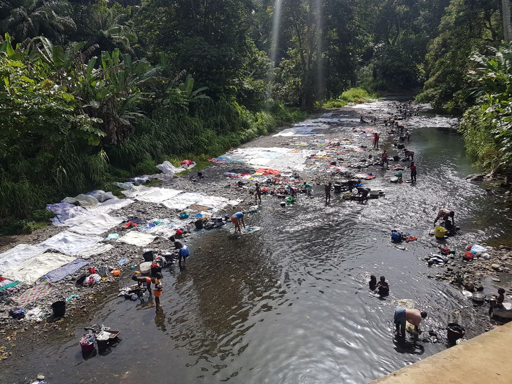 Women washing clothes in a stream at Sao Tome