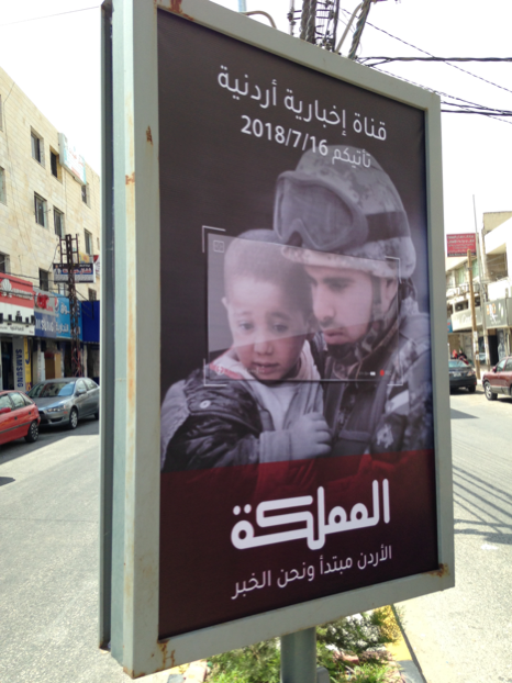 """A news channel called """"The Kingdom"""" ran an ad showing a Jordanian soldier in full battle dress uniform and helmet carrying a Syrian refugee baby girl in his arms. It reflects the widespread Jordanian trust and admiration of a King and his security apparatus that are credited with providing relative calm in a chaotic region."""