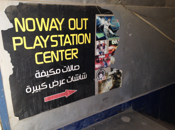 """The ominously named """"No Way Out Playstation Center"""" hires young men to stand on the street pressuring passersby to enter."""
