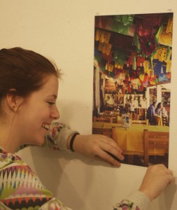 Jenn Smulo hanging a photo of Mexico City in the FORM gallery