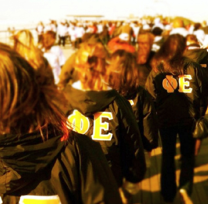 Phi Epsilon, donning their black and gold jackets, on the boardwalk at Jones Beach. Photo courtesy of Phi Epsilon's Twitter.