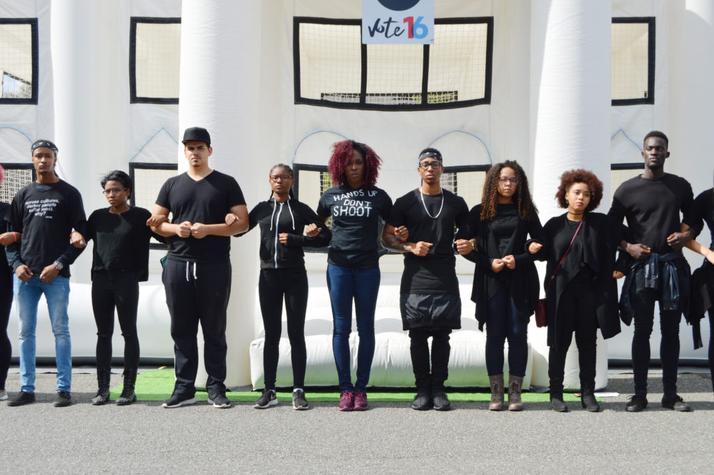 Students from the Black Student Union link arms in front of a White House bounce castle in protest of the fatal shootings of black Americans by police. (Photo by Cam Keough/The Chronicle)