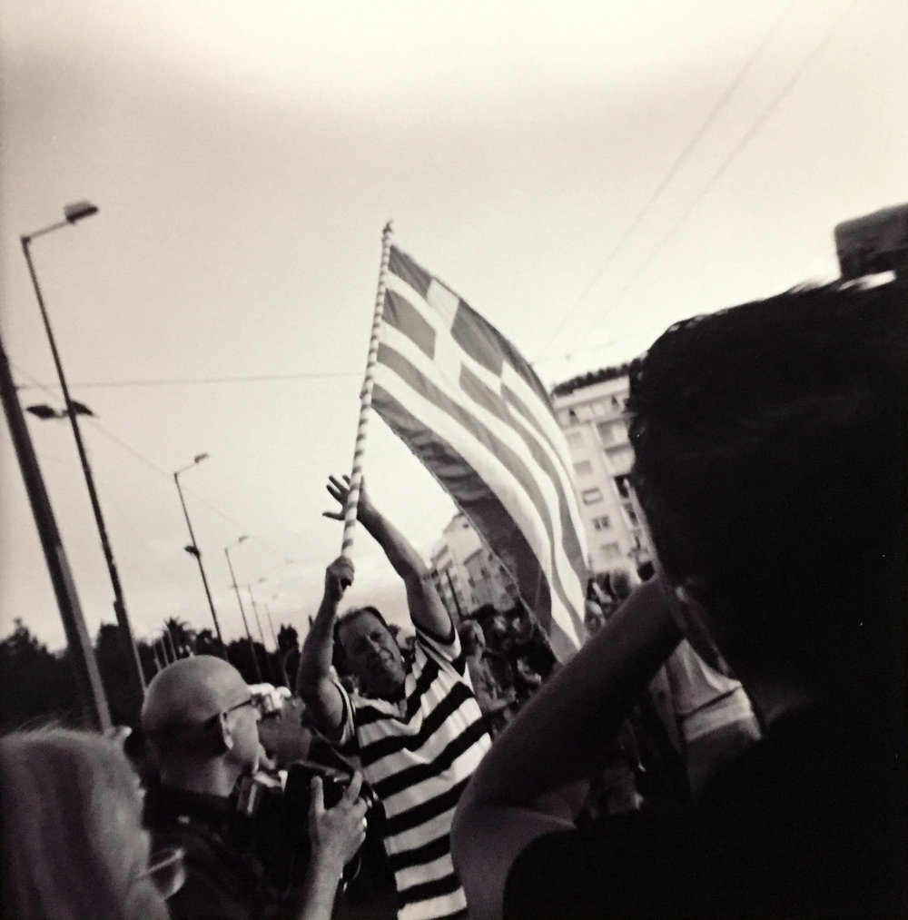 Protester waves a flag outside the Greek Parliament Building in Athens.
