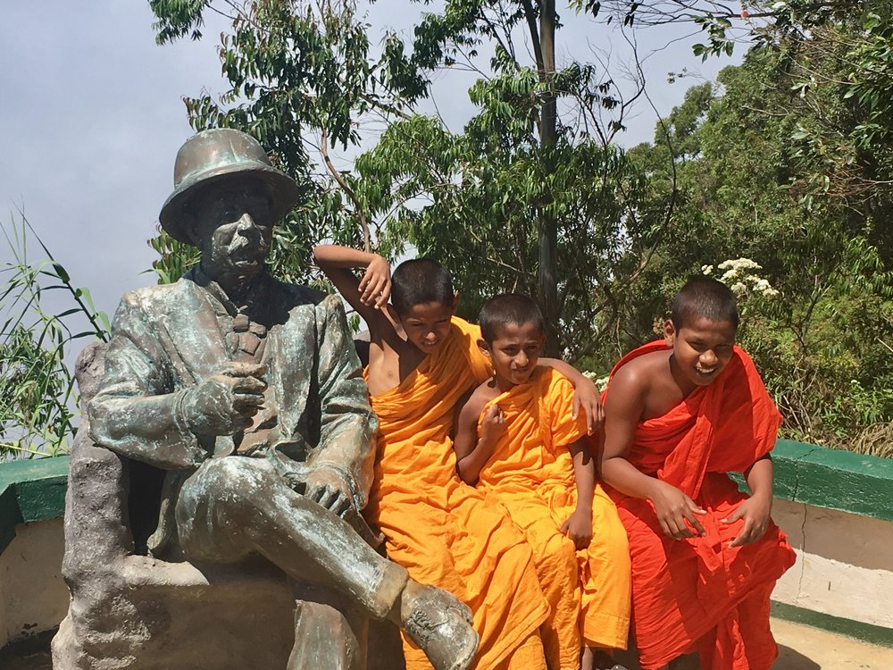 "Young monks join tea pioneer Thomas Lipton at the site of ""Lipton's Seat,"" where Sir Thomas would sit and look out over production at his Dambatenne Tea Estate."