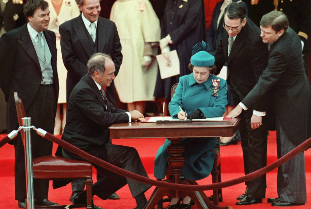 Prime Minister Pierre Trudeau watches as Queen Elizabeth II signs Canada's new Constitution.