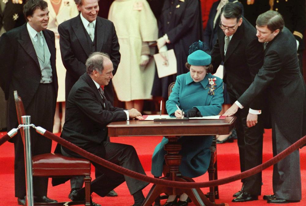 La reine Elisabeth II signe la nouvelle Constitution.