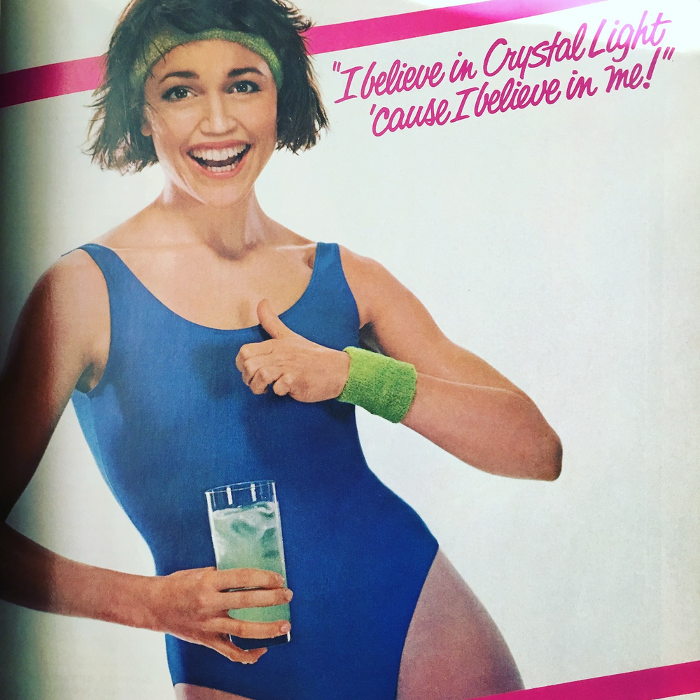 """I believe in Crystal Light 'cause I believe in me!"" The jingle is now going to be stuck in my head all day with visions of 80s aerobics videos.  Glamour. July 1984. The aerobics fad of the '80s was defintely a major phenomenon. Everything from the 1981 Olivia Newton John ""Let's Get Physical"" video (double entendre notwithstanding), to Great Shape Barbie from 1983 - the fitness craze was pretty much sweeping the nation, and of course marketers decided to capitalize on low-sugar, low-fat, diet products. Crystal Light was introduced in 1982 and was targeted toward health-conscious women, leotard, sweatband and all."