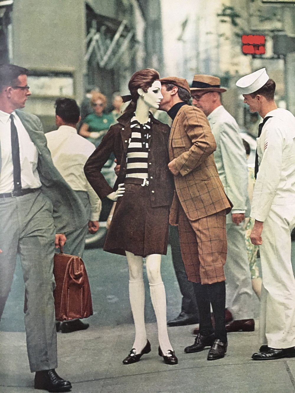 The newly nifty knee sock. The mannequin underscores her culotte suit of brown suede and striped jersey shirt with snappy white knee socks. The man displays a shapely calf in a new-again knicker suit.