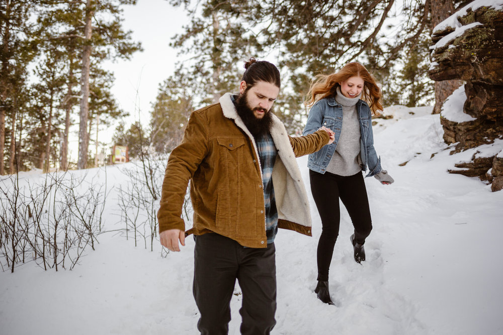 couple walking in snow engagement photos