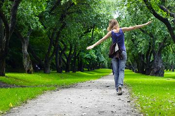 bigstock-Woman-walking-on-path-in-green-140210001