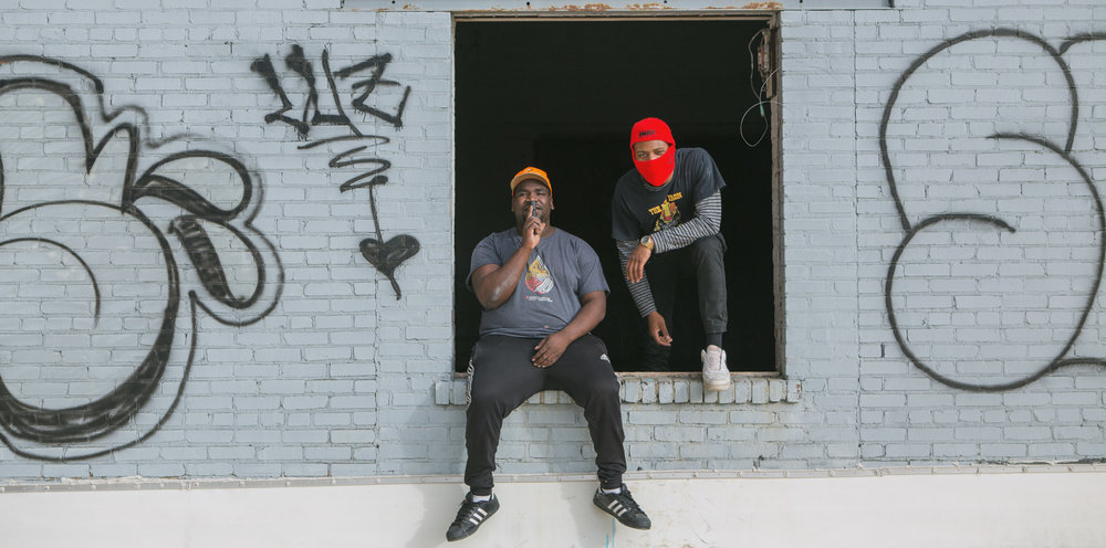 Image of two guys siting in a broken window frame