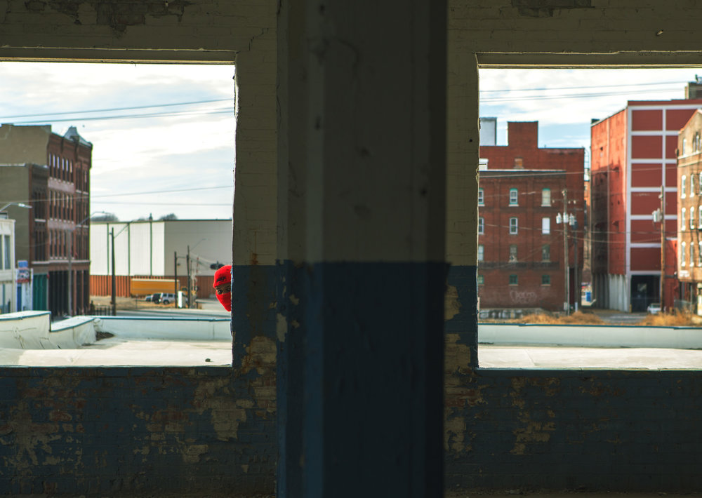 Image of a guy hiding behind a wall and looking through a broken window frame