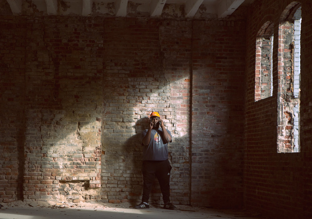 Image of man standing against a red brick wall on the cellphone with a gun