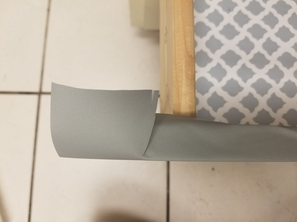 Cut a small slit level with the corner of the cabinet at the same angle. You will be creating a dog ear to tuck it around the corner.