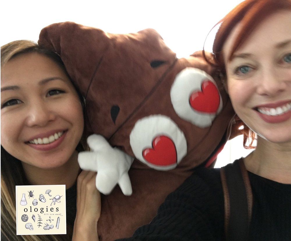 Dr. Elaine Hsiao poses with a poop emoji shaped pillow and also Alie Ward