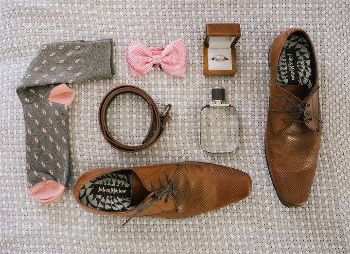 Grooms attire laid out pastel pinks socks, bow tie, brown leather shoes and belt wedding rings and cologne