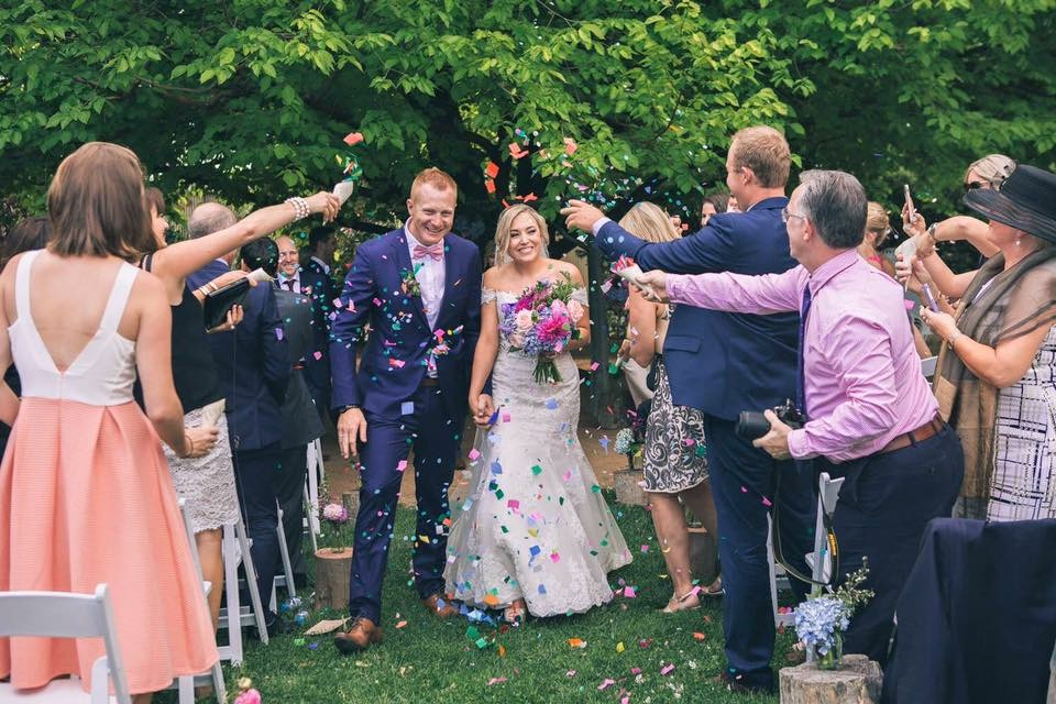 Bride and groom celebrate their marriage confetti thrown above them