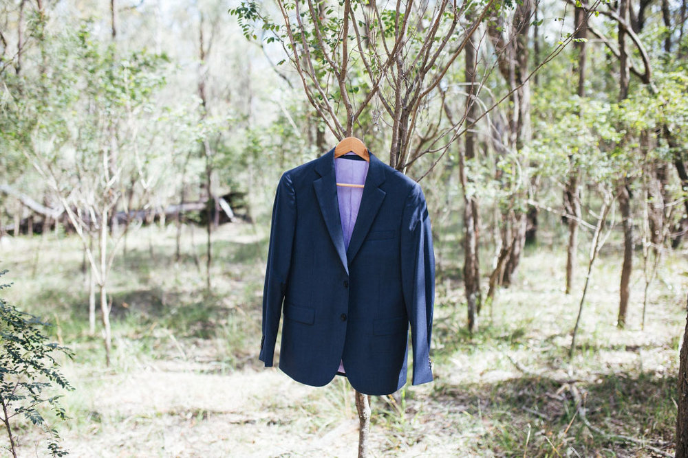 Groom's suit jacket hanging at wedding ceremony location