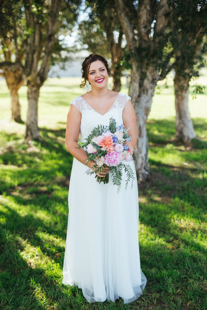 Beautiful bride in a white dress on the grass with her bouquet